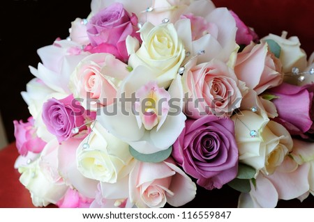 Brides bouquet of purple and pink roses and orchid