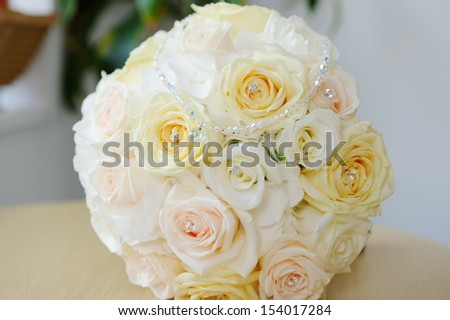 Brides bouquet of yellow roses and heart shaped pendant on necklace closeup detail - stock photo
