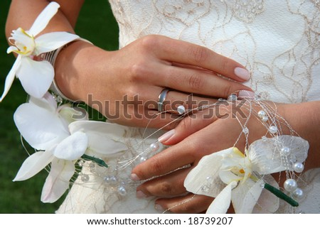 Brides hands with the rind and flowers - stock photo