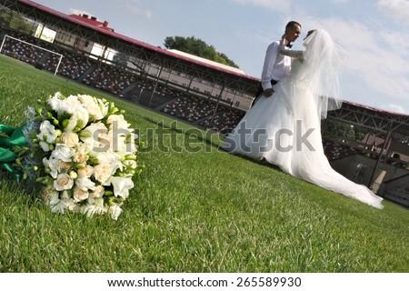 Brides on a football field .  gentle kiss. loving feelings. bridal bouquet. - stock photo