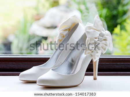 Brides shoes closeup on wedding day by a window