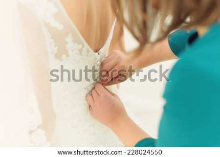 bridesmaid buttoning lace wedding dress - stock photo