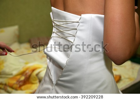 bridesmaid dress from the back in the process of dressing  - stock photo
