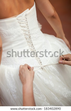 Bridesmaid helping the bride to put her wedding dress on. Tying bow on wedding dress - stock photo
