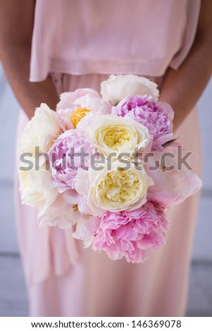 Bridesmaid Holding a Bouquet with Peonies - stock photo