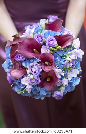 Bridesmaid holding blue and purple wedding bouquet against dress - stock photo