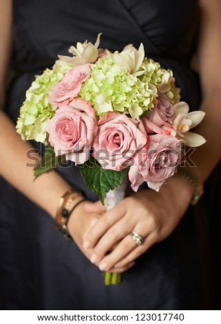 Bridesmaid holding pink and green wedding bouquet - stock photo
