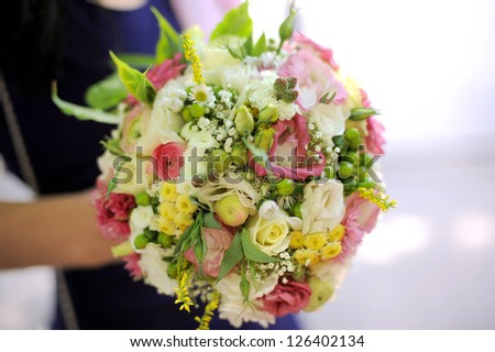 bridesmaid holding wedding bouquet in park - stock photo