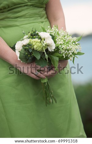Bridesmaid holding wedding bouquets against green dress - stock photo