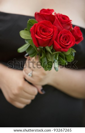 Bridesmaid holding wedding flower bouquet of red roses - stock photo