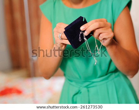bridesmaid holding wedding jewelry in hands - stock photo