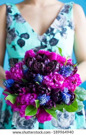 bridesmaid holds a wedding bouquet of tulips and pions in purple tones - stock photo