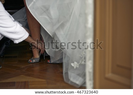 Bridesmaid is holding a wedding shoe of the bride