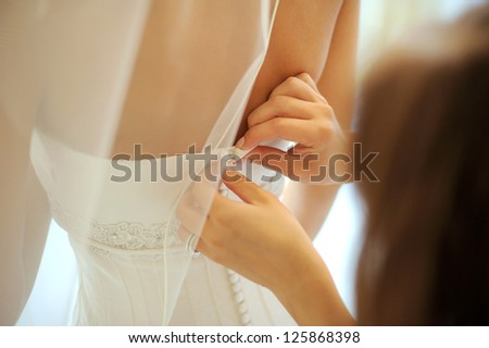 bridesmaid's hands buttons wedding dress - stock photo
