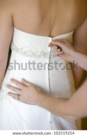 bridesmaid zips up the wedding dress of the bride