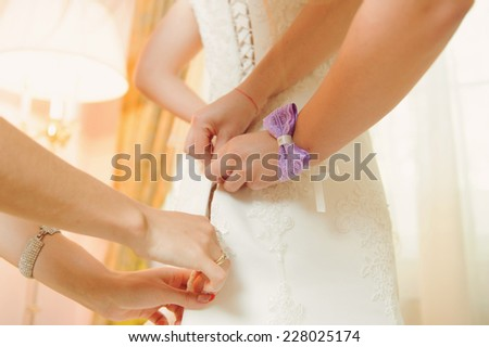 bridesmaids helping bride to tie corset on dress - stock photo