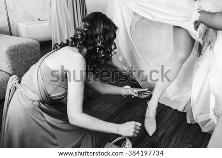 Bridesmaids helping young bride before the wedding ceremony - stock photo
