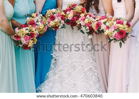 Bridesmaids hold their wedding bouquets before a bride