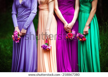 Bridesmaids in colorful dresses with bouquets of flowers - stock photo
