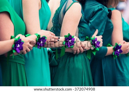bridesmaids in green dresses with violet bracelets on hands - stock photo