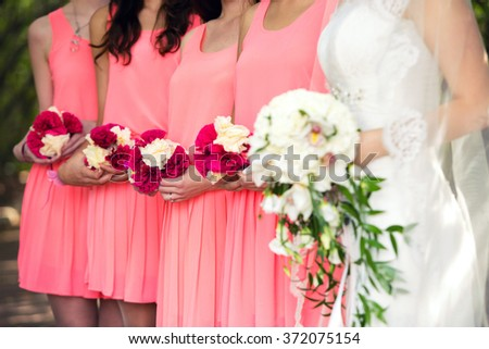bridesmaids in pink dresses and the bride with a bouquet - stock photo