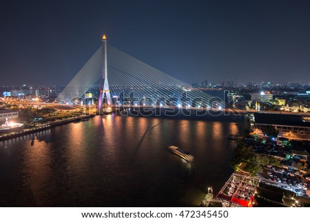 Bridge across Chao Phraya river at twilight in Bangkok, Thailand
