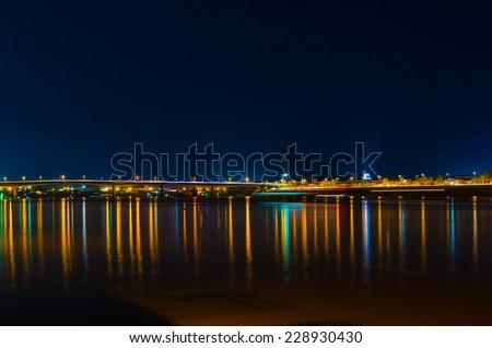 bridge and embankment lights reflect in Tonle Sap river - stock photo