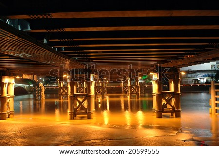 Bridge by night, photo taken under the bridge showing bridge's pillars and reflections from water. Ningbo city, China.