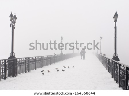 Bridge city landscape in foggy snowy winter day - walking couple, lanterns and doves flock - Ukraine, Donetsk - stock photo