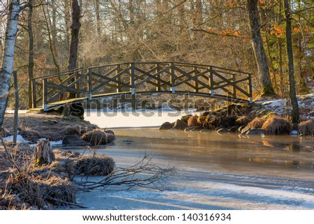Bridge connecting opposite shores of a lake at a narrow point. - stock photo