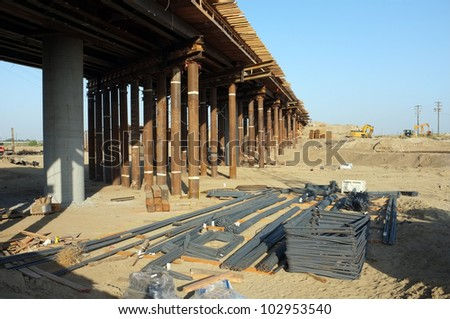Bridge Construction Project: Reinforcing steel bars lay on ground ready strengthen structure as temporary wood bracing and steel shoring support roadway beams before concrete is poured - stock photo