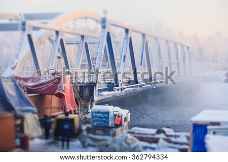 Bridge construction site, over the river in a cold winter day, bridge under construction in progress - stock photo