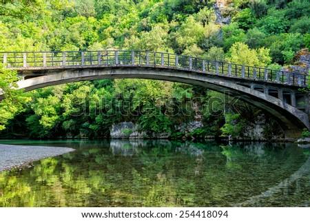 Bridge in bright forest of Voidomatis river that flows through Epirus region, Greece. Natural composition - stock photo