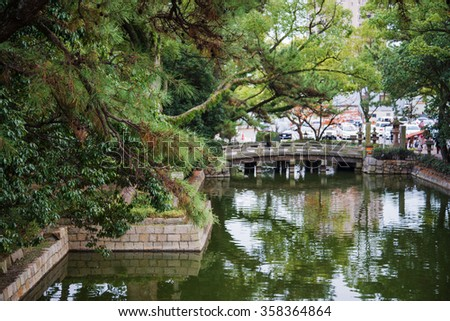 bridge in garden with reflect shadow on water - stock photo