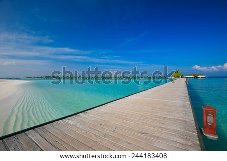 Bridge leading to overwater bungalow in blue lagoon around tropical island - stock photo