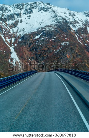 Bridge on the Norwegian road in the snowbound mountains - stock photo