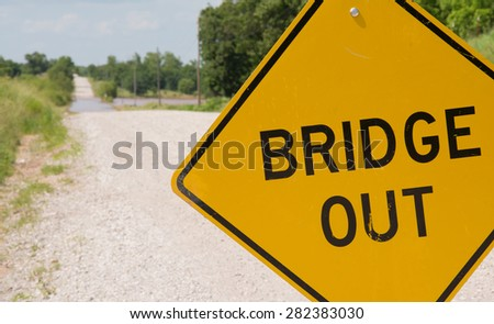 Bridge out -sign ahead of a flooding covered road warning drivers - stock photo