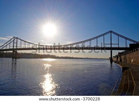 bridge over blue river and rising sun - stock photo