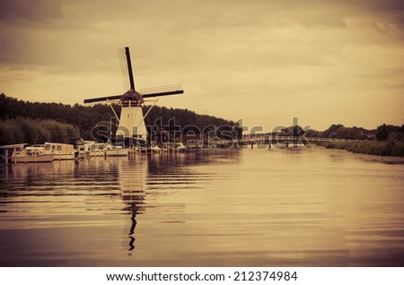 Bridge over channel near Historic Dutch windmill in  Alblasserdam, Netherlands - stock photo