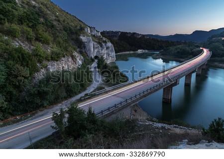 Bridge over lake in the mountains - stock photo