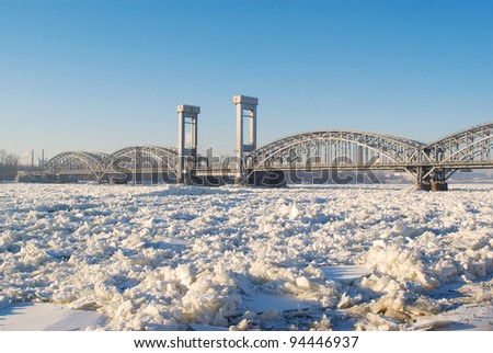 Bridge over the frozen river in sunny day