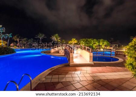 Bridge over the swimming pool at luxury caribbean resort at night, dawn time. Bahia Principe, Riviera Maya, Mexican Resort. - stock photo