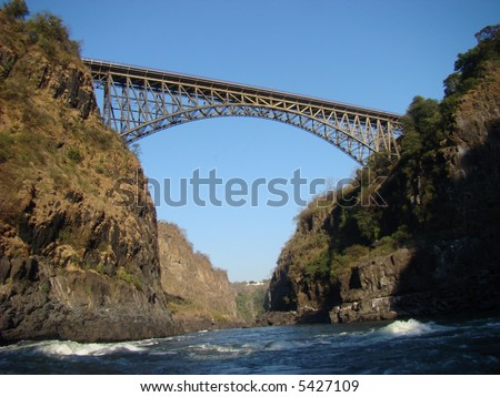 Bridge over the Zambezi River connecting Zambia and Zimbabwe at Victoria Falls. Location of the highest commercial bungee jump in the world. - stock photo