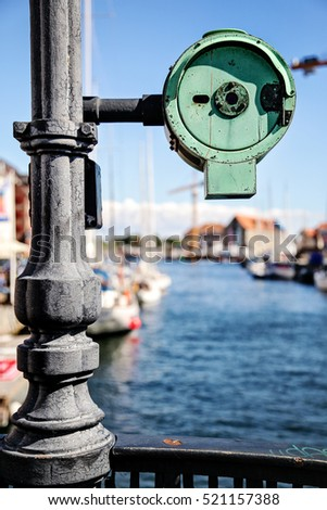 Bridge pillar with round metal detail attached to it. It is isolated against background. Photo is taken in Copenhagen city center, view on a canal. Sunny august day in Denmark