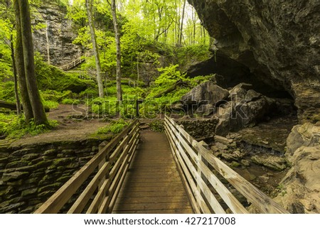 Bridge To Cave / A footbridge leading to a cave entrance. - stock photo