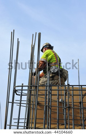 Bridge widening construction project: Workman ties reinforcing bars in concrete forms - stock photo