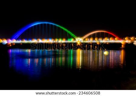 bridge with rainbow color light at night - stock photo