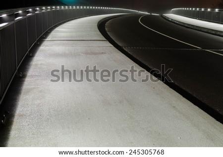 Bridge with street and illuminated railing at night - stock photo