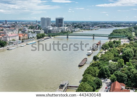 Bridges over the Danube river in Bratislava city, Slovak republic. Docks scene. Old bridge and Apollo bridge. Ship transportation. High-rise buildings. Travel destination. - stock photo