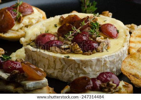 Brie cheese baked with nuts and grapes, tasty and crispy baguette and bio herbs, reduction of sugar, nuts and balsamic vinegar - stock photo